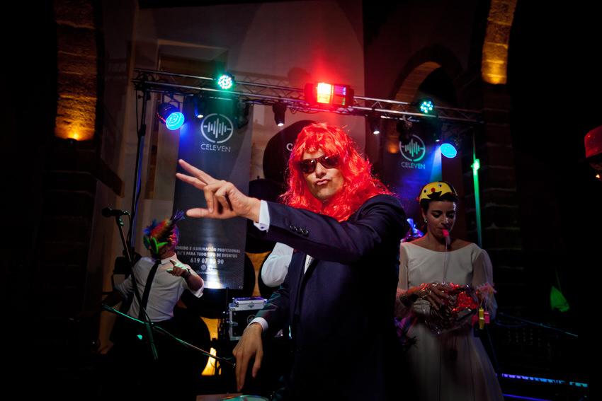 novio con una peluca roja divertiendose en su fiesta de boda